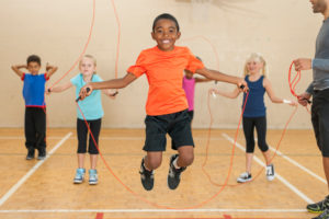 Diverse elementary gym class playing with skipping ropes