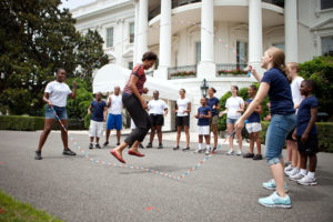 First Lady Michelle Obama and kids double-dutch jump rope during a taping for the Presidential Active Lifestyle Award (PALA) challenge and Nickelodeon's Worldwide Day of Play, on the South Lawn of the White House, July 15, 2011. (Official White House Photo by Chuck Kennedy) This official White House photograph is being made available only for publication by news organizations and/or for personal use printing by the subject(s) of the photograph. The photograph may not be manipulated in any way and may not be used in commercial or political materials, advertisements, emails, products, promotions that in any way suggests approval or endorsement of the President, the First Family, or the White House.